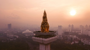 Sunset view of Jakarta's National Monument's gold-layered torch.