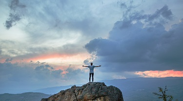 Man standing on top of a mountain with his arms in the air.