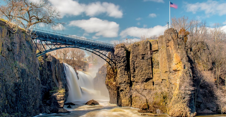 Bridge spanning rushing water with U.S. flag flapping in the wind