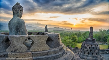 A sunset view of the ancient Borobudur temple complex in Central Java