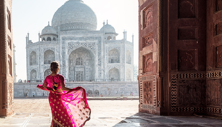 A woman in a sari dances in front of an ornate entrance with a view of the Taj Mahal.