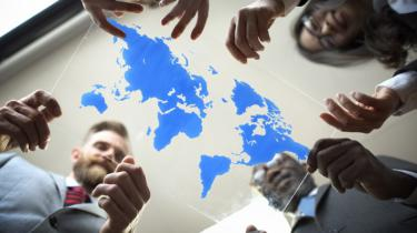 Business colleagues gather around world map image etched on glass.