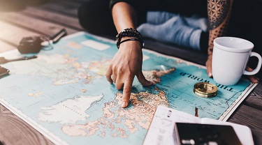 There is a world map on a coffee table. Someone is pointing to North America on the map.