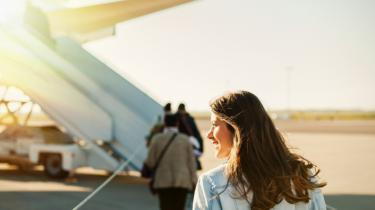 Radiant female exporter walks across tarmac to board plane.