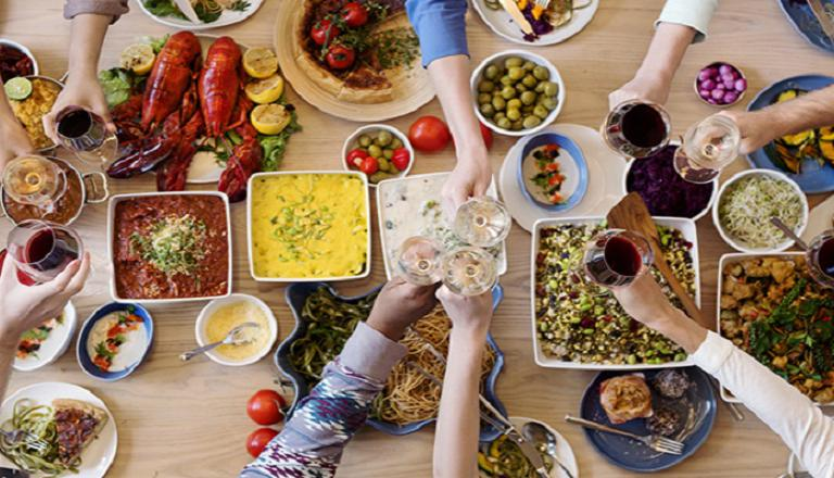 A table loaded with food from many different cultures, and hands reaching in towards the food.