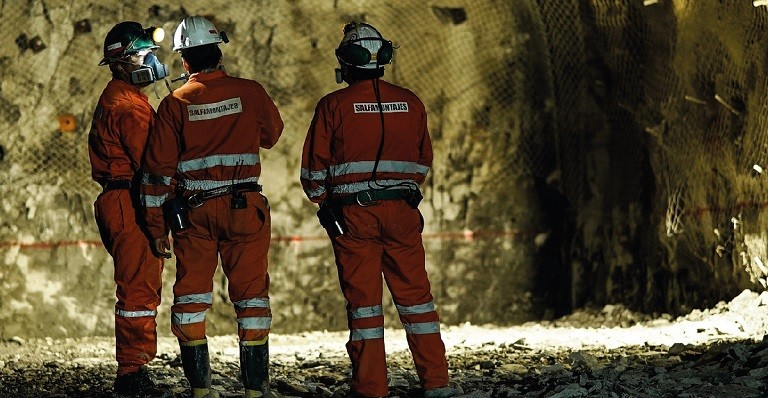 Three Codelco employees in protective gear survey a copper mine.