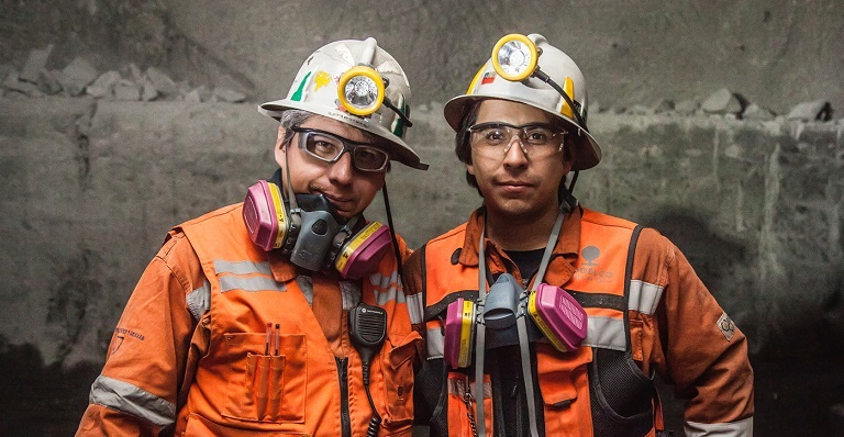 Two Codelco employees in protective gear smile for the camera as they stand in a copper mine.