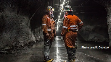 Two Codelco employees in protective gear stand in a copper mine having a discussion.