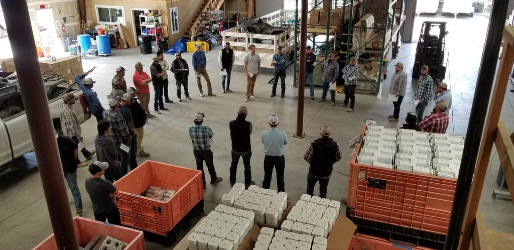 Management and workers gathered in the warehouse