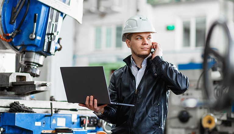 An engineer standing in front of an industrial machine with his laptop talks on the phone