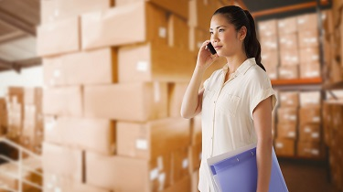 A businesswoman is standing in a stockroom and talking on the phone.