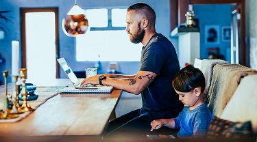 Man at a desk on his laptop with his young daughter sitting beside him.