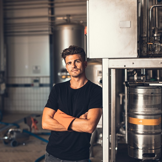 A microbrewery owner stands next to industrial equipment.