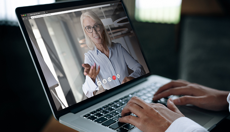 A businessman speaks on a web conference with an advisor using a laptop webcam.