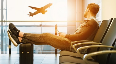 Man in airport watching plane take off