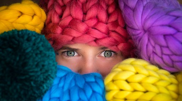 An entrepreneur peeks out from behind her colourful wool inventory.