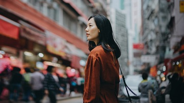 A woman stands on a busy street, surrounded by tall buildings and looking pensive.