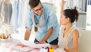 Male, female fashion designers work in studio