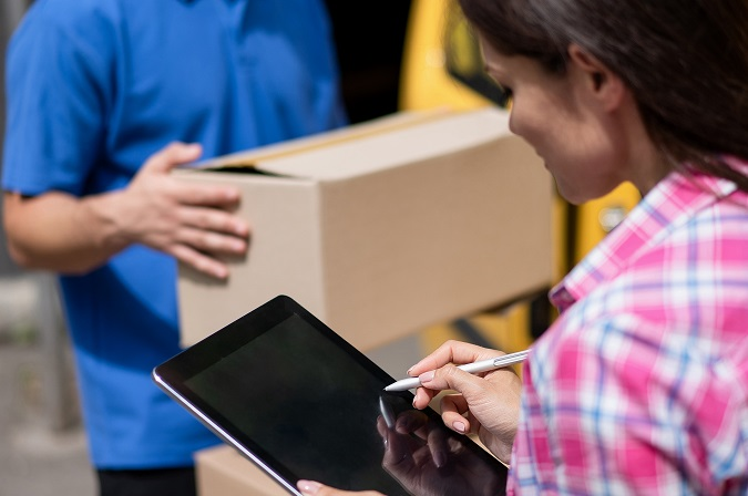 Two people stand in a warehouse discussing shipping.Waybill and shipping documentation are completed by a woman on tablet while man carries shipment.