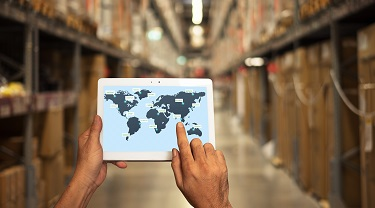Man in a warehouse with tablet showing the map of the world where the goods will be delivered.