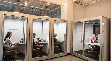 SnapCab's modular, enclosed pods being used in an open workspace environment for privacy and noise reduction.