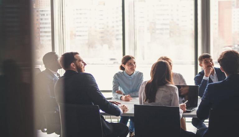 Employees collaborating at a board room table to be more competitive globally
