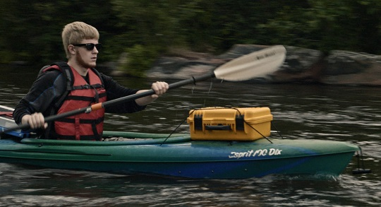 Man monitoring water while kayaking