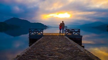 Couple on a dock looking out at the lake during sunset.