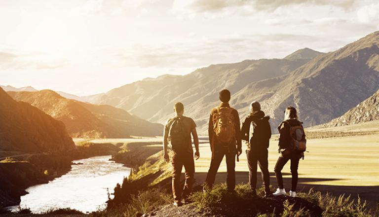 A team of hikers surveys a mountainous landscape to strategize their way forward.