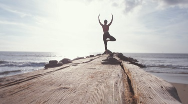 Woman doing yoga at the end of a dock.