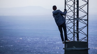 Man climbs up radio tower overlooking open water