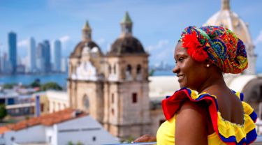 Colombian woman in colourful dress with buildings in background
