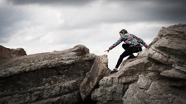 Female hiker attempts a risky manoeuvre while climbing between two rocks.