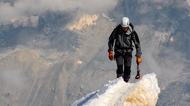 Male climber tackles dangerous snowy mountaintop