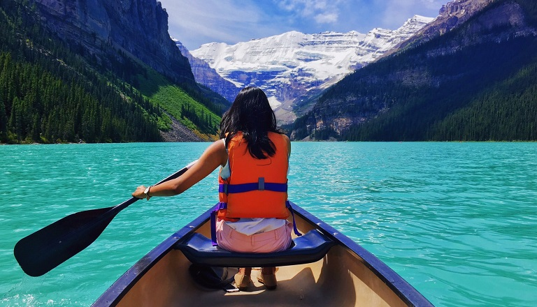 Female paddles in canoe on Moraine Lake