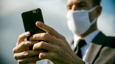 Business man wearing surgical mask sends text on his cellphone