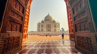 Man stands in courtyard admiring India's Taj Mahal