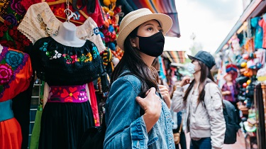 Women wearing masks browse Mexican market
