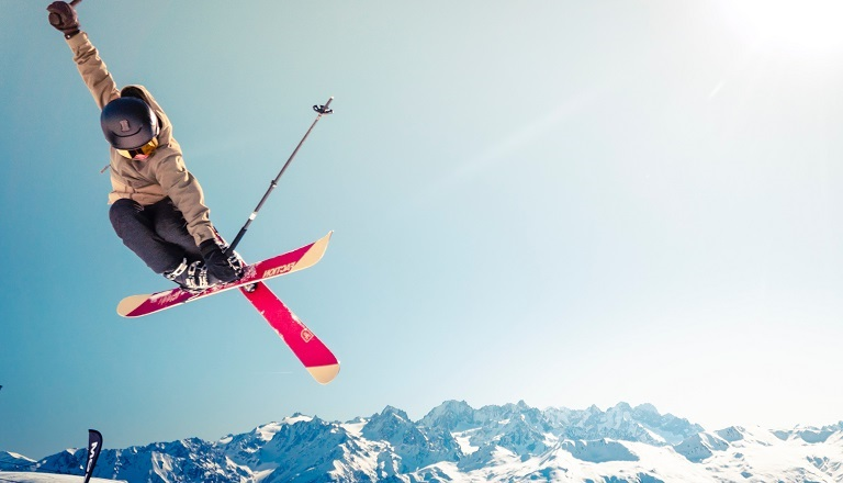 A skier takes an impressive leap on a bright, snowy hilltop.