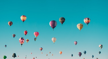 Hot air balloons dot the sky.