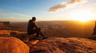 Hiker watching the sunset at Grand View Point in Canyonlands National Park in Utah, USA