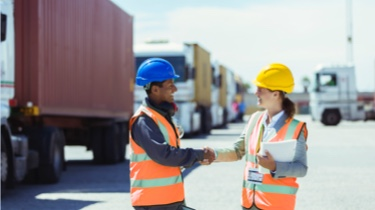 A man and a woman wearing construction hats shake hands and smile.