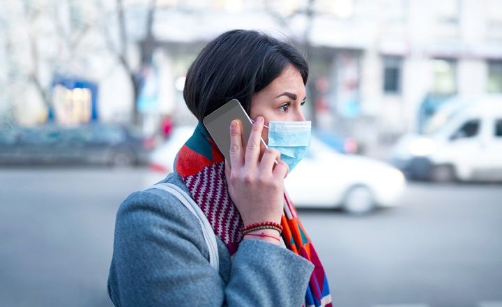 Photo of a professional woman wearing a facemask talking on the phone