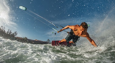 Action shot of man kiteboarding among waves