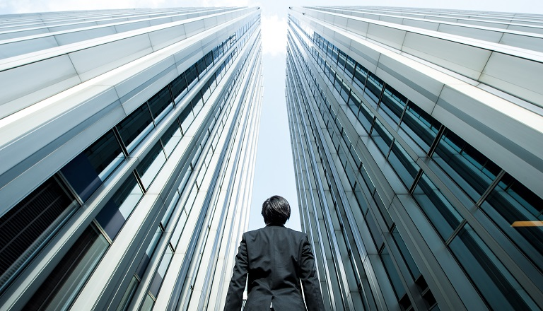 Businessman surrounded by tall steel buildings looks to the sky