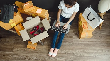 woman on laptop surrounded by shipping boxes