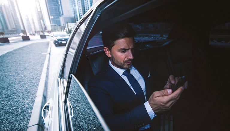 Worried businessman checks phone while driving in a limo