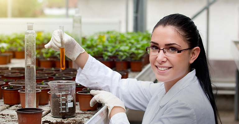A woman biologist looks at plant samples