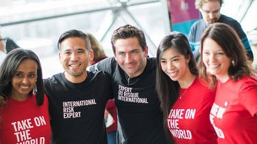 "Diverse EDC employees wearing shirts that say ""Take on the World"" and ""International Risk Expert"""