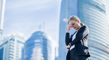 Stressed businesswoman looks upset and holds head in her hand outside of her workplace.